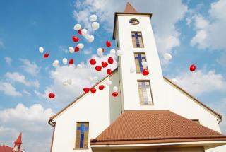 balony z helem na tle kościoła, atrakcje na ślub, wypuszczenie balonów w niebo